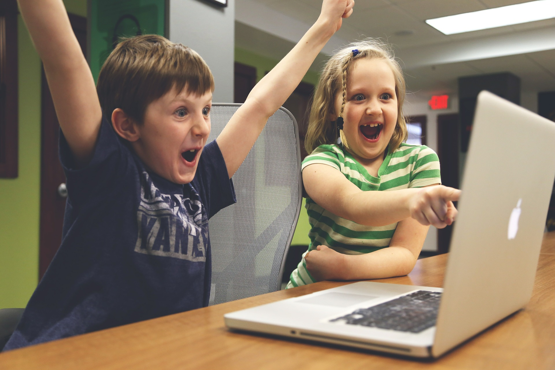 two children excited in front of laptop