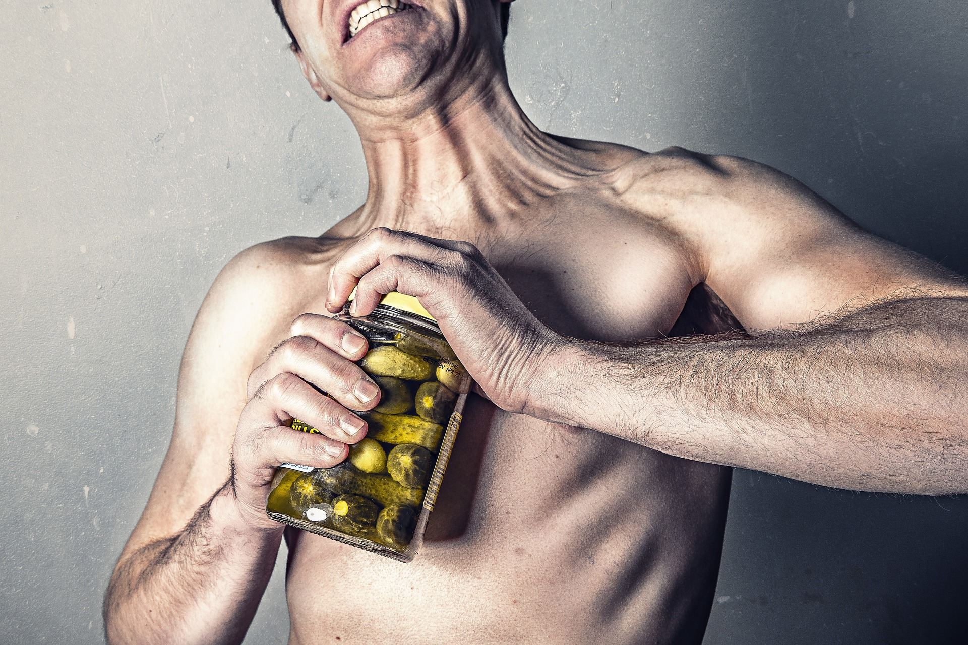 shirtless man attempting to open jar