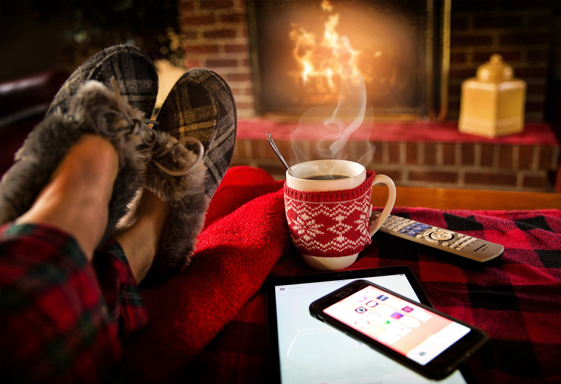 feet in slippers on table in front of fireplace with mug